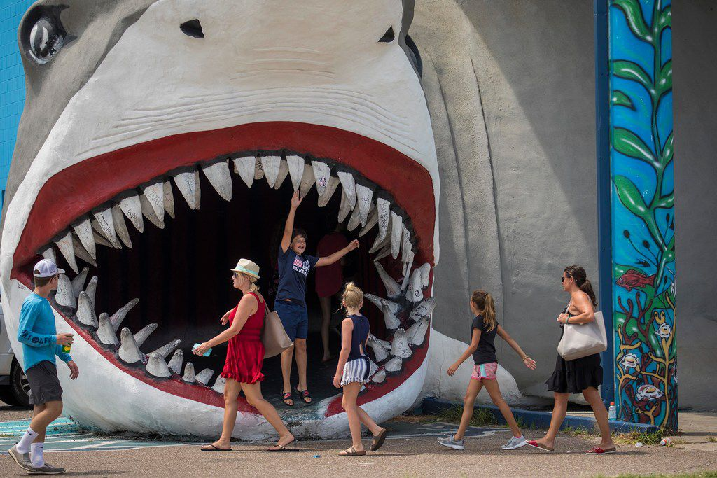 Tourists visit the iconic shark at Destination Beach and Surf shop in Port Aransas on the Texas Gulf Coast.