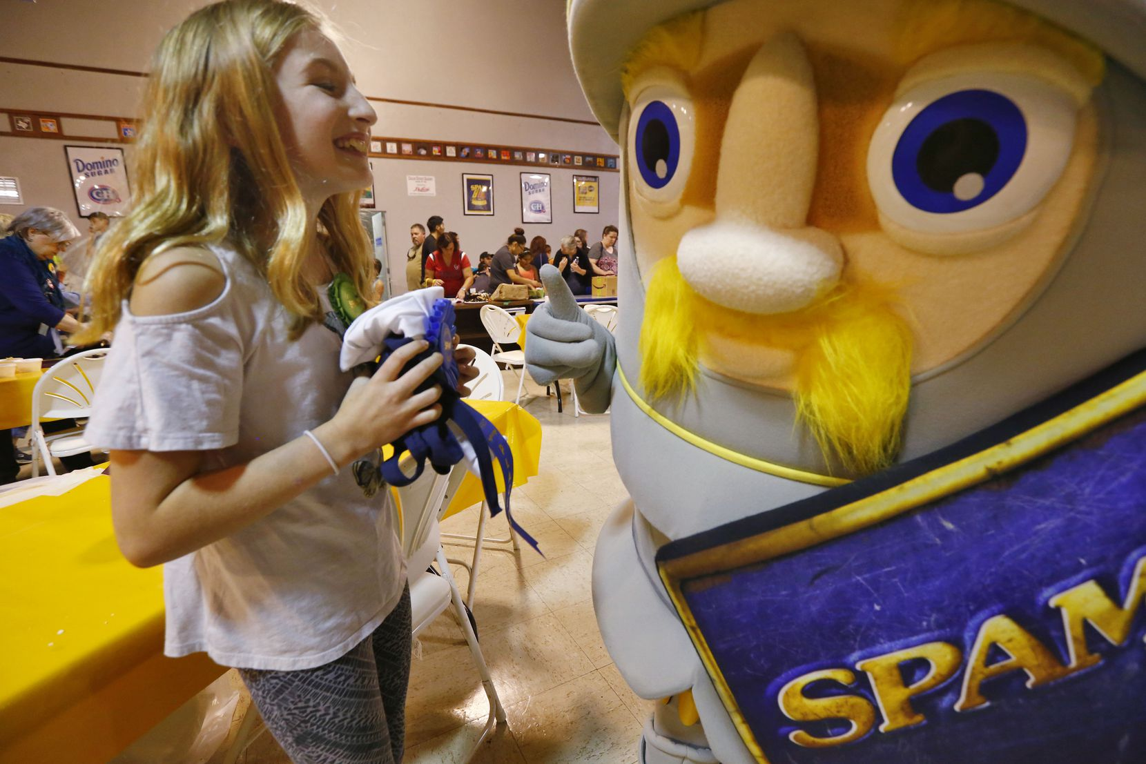 Allyson Garmon, 11, laughs with the Spam mascot, Sir Can-A-Lot, after winning the Kid Chef Spam cooking contest.