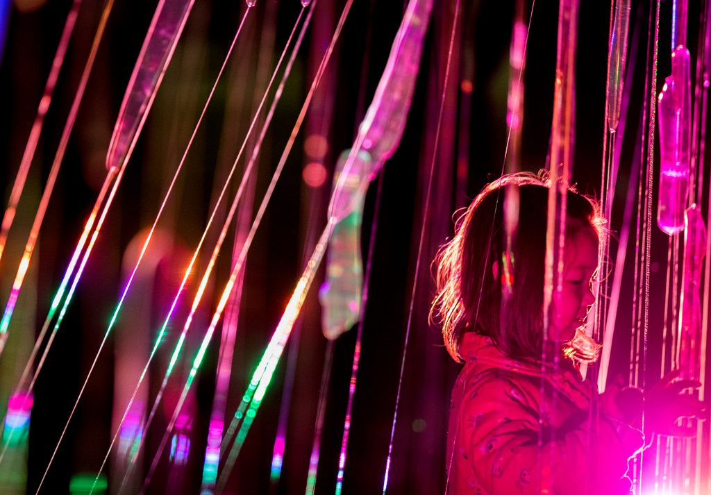 """Texana Tennison 3, of Grapevine, Texas touches """"Freezing Rain"""" by Paula Crown during Aurora in Dallas on Nov. 3, 2018. The free art exhibition focuses on on light, video and sound art."""