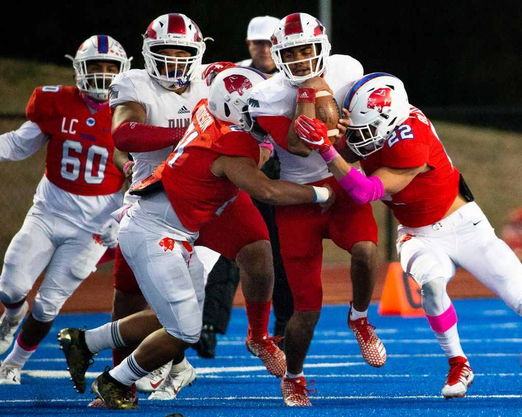 Bishop Dunne quarterback Simeon Evans (center, 1) gets taken down by Parish Episcopal linebacker Keegon Addison (21) and defensive lineman Colby Blatnick (22) during the football game between Parish Episcopal High School and Bishop Dunne Catholic School at the Gloria H. Snyder Stadium in Farmers Branch, Texas, on Friday, Oct. 11, 2019. (Lynda M. Gonzalez/The Dallas Morning News)