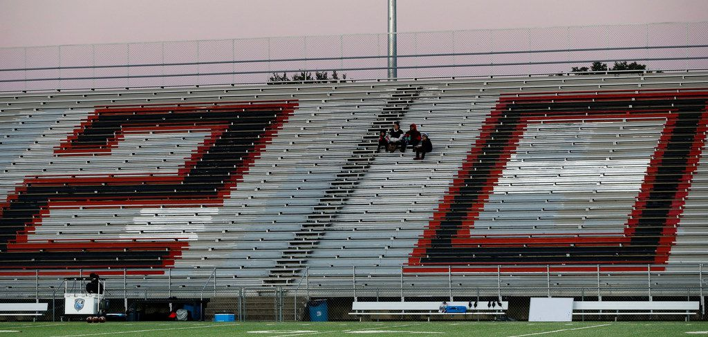 """Early arriving North Dallas High fans sit in the middle of a giant number """"20"""" painted on the stands... the graduation year of Hillcrest High's senior class (the stadium is adjacent to Hillcrest high)... before the teams high school football game at Franklin Stadium in Dallas on Friday, October 11, 2019. (John F. Rhodes / Special Contributor)"""