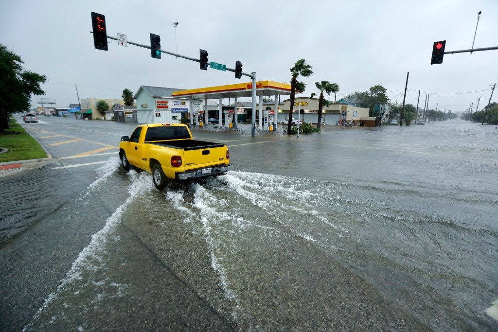 Pickup trucks navigate flooded Broadway Ave., the main drive through Galveston, Texas,Tuesday, August 29, 2017. The city was flooded from punishing overnight rains from Tropical Storm Harvey which passed by the island, Tuesday.(Tom Fox/The Dallas Morning News)
