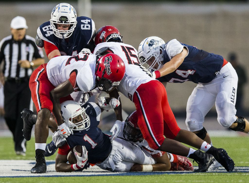 Allen running back Celdon Manning (1) is taken down by Cedar Hill defenders during the second quarter of a high school football game between Allen and Cedar Hill on Friday, August 30, 2019 at Eagle Stadium in Allen. (Ashley Landis/The Dallas Morning News)