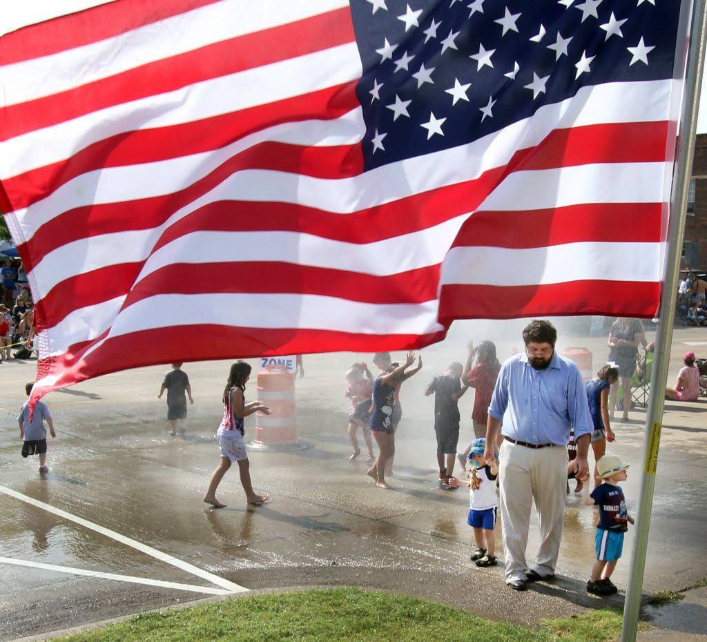 """Framed by an American Flag, Jacob Wallace, of Midlothian, accompanies his 2-year-old sons, Henry Wallace, left, and Alexander Wallace following a brief visit to the designated """"wet area"""" (compliments of an aerial ladder truck), just prior to the start of Midlothian's annual 4th of July parade which was held in the downtown Midlothian area on July 4, 2015. {Steve Hamm/Special Contributor)"""