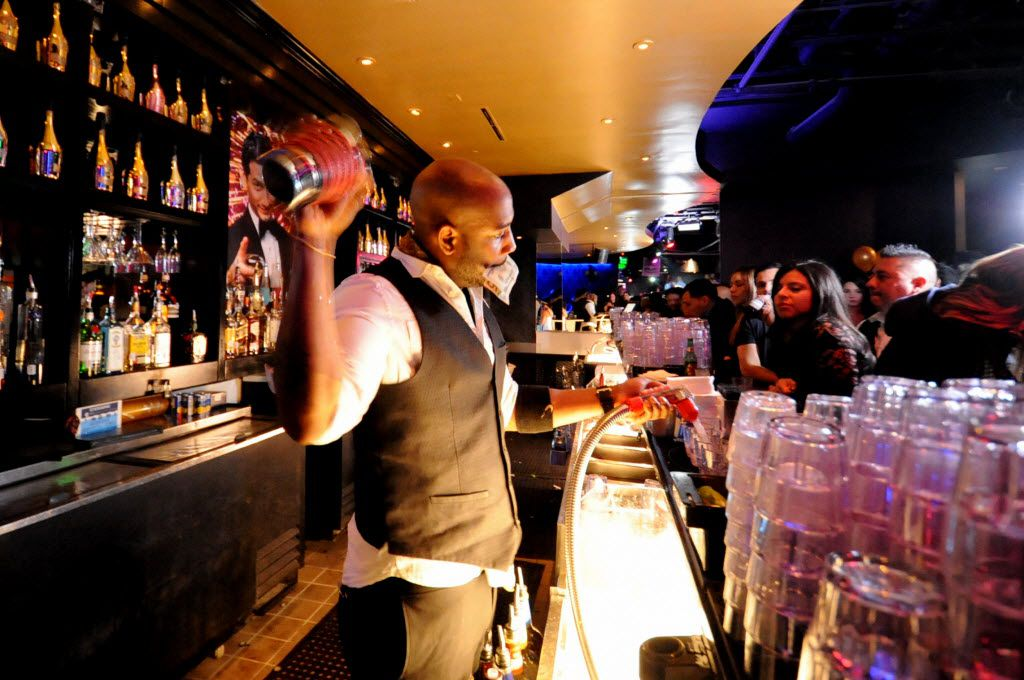 A busy bartender multitasks at the new nightclub Gatsby in Dallas, TX on March 6, 2015.