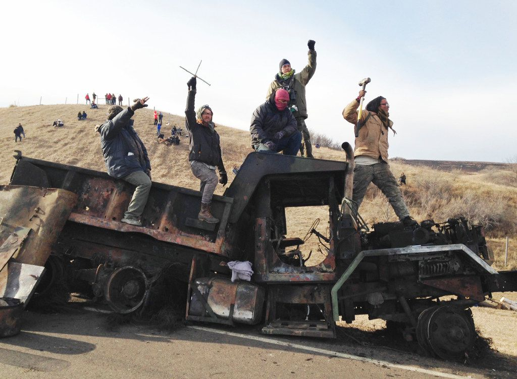 In this Monday, Nov. 21, 2016, file photo, protesters against the Dakota Access oil pipeline stand on a burned-out truck near Cannon Ball, N.D., that they removed from a long-closed bridge a day earlier on a state highway near their camp in southern North Dakota.  (AP Photo/James MacPherson, File)