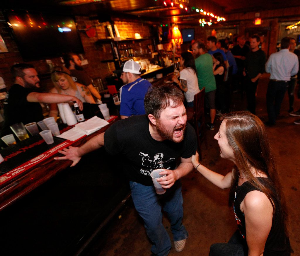 Kevin Huckabee and Stephanie Evola sing to a 'Guns & Roses' song during the last hours of operation of the Elbow Room in Dallas on April 16, 2017. (Nathan Hunsinger/The Dallas Morning News)