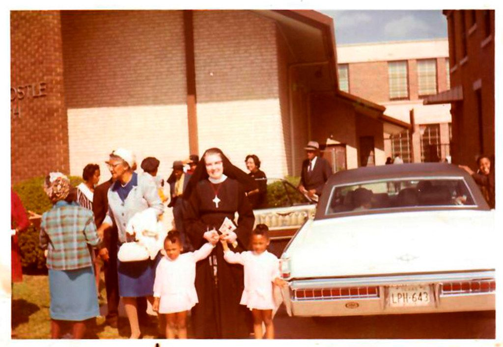 An unidentified nun, a member of the Sisters of the Holy Ghost order (now the Holy Spirit order), holds the hands of 4-year-old Micaela (left) and Myrna Dartson at St. Peter the Apostle Catholic Church in Dallas. The nun taught at St. Peter's Catholic school.