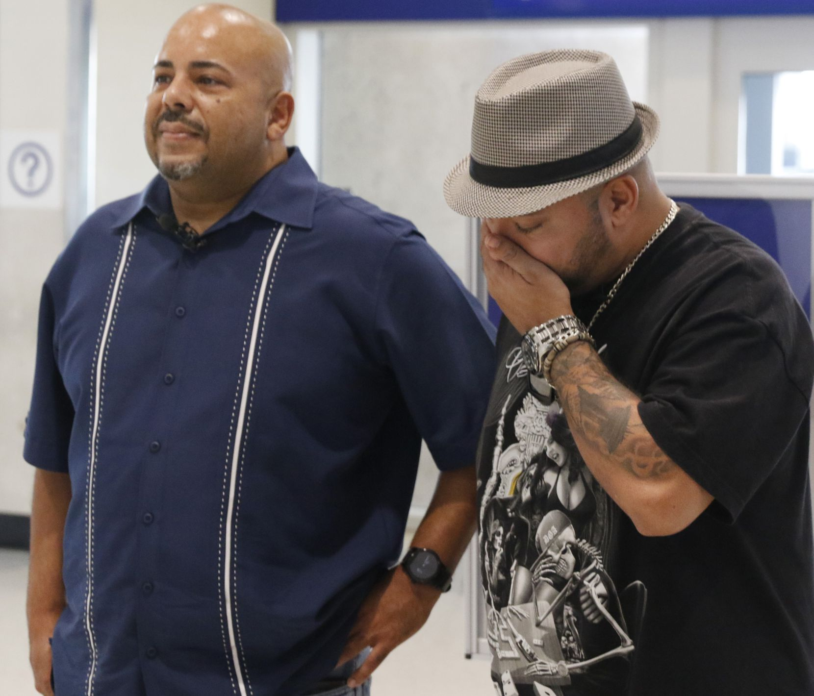 Anthony Wiggs (left) and Raymond Ramirez wait to meet their biological mother, Elsie Ramirez, for the first time at DFW Airport.
