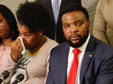 Amber Carr, center, wipes a tear as her sister, Ashley Carr, left, and attorney Lee Merritt, right, listen to their brother Adarius Carr talk about their sister, Atatiana Jefferson during a press conference at 1910 Pacific on Monday morning, October 14, 2019 in downtown Dallas. Atatiana Jefferson, a 28-year-old black woman, was shot and killed in her home by a white Fort Worth police officer during a welfare check. (Irwin Thompson/The Dallas Morning News)