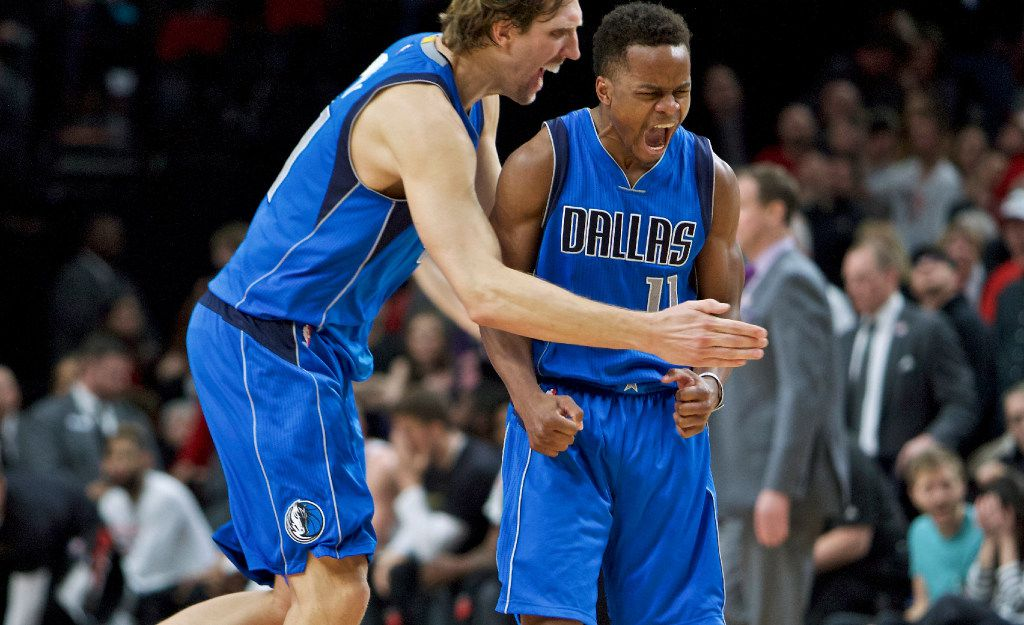 Dallas Mavericks guard Yogi Ferrell, right, and forward Dirk Nowitzki react after Ferrell made a 3-point basket against the Portland Trail Blazers during the second half of an NBA basketball game in Portland, Ore., Friday, Feb. 3, 2017. (AP Photo/Craig Mitchelldyer)