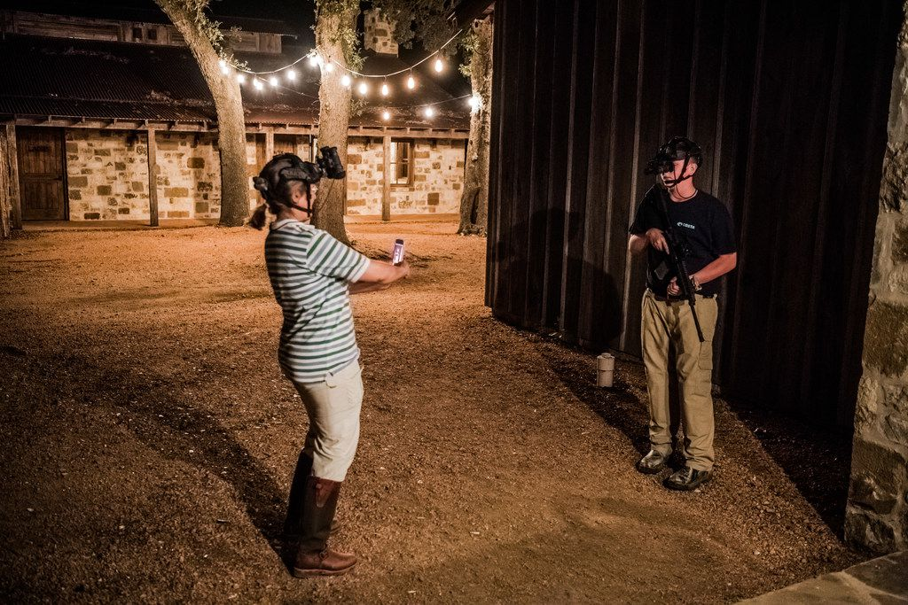 Joan Schaan takes a photo of her son Daniel Schaan, 15, as he prepares for a night boar hunt at the Ox Ranch in Uvalde, Texas, Aug. 17, 2017.