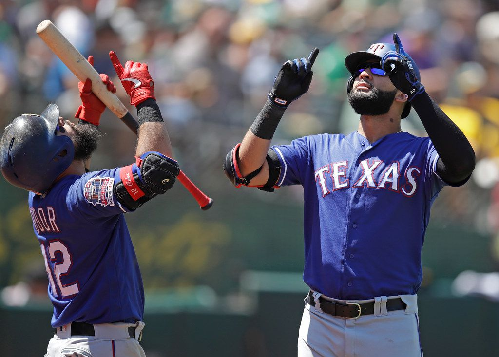 Texas Rangers' Nomar Mazara, right, celebrates with Rougned Odor (12) after hitting a home run off Oakland Athletics' Mike Fiers in the sixth inning of a baseball game Sunday, July 28, 2019, in Oakland, Calif. (AP Photo/Ben Margot)