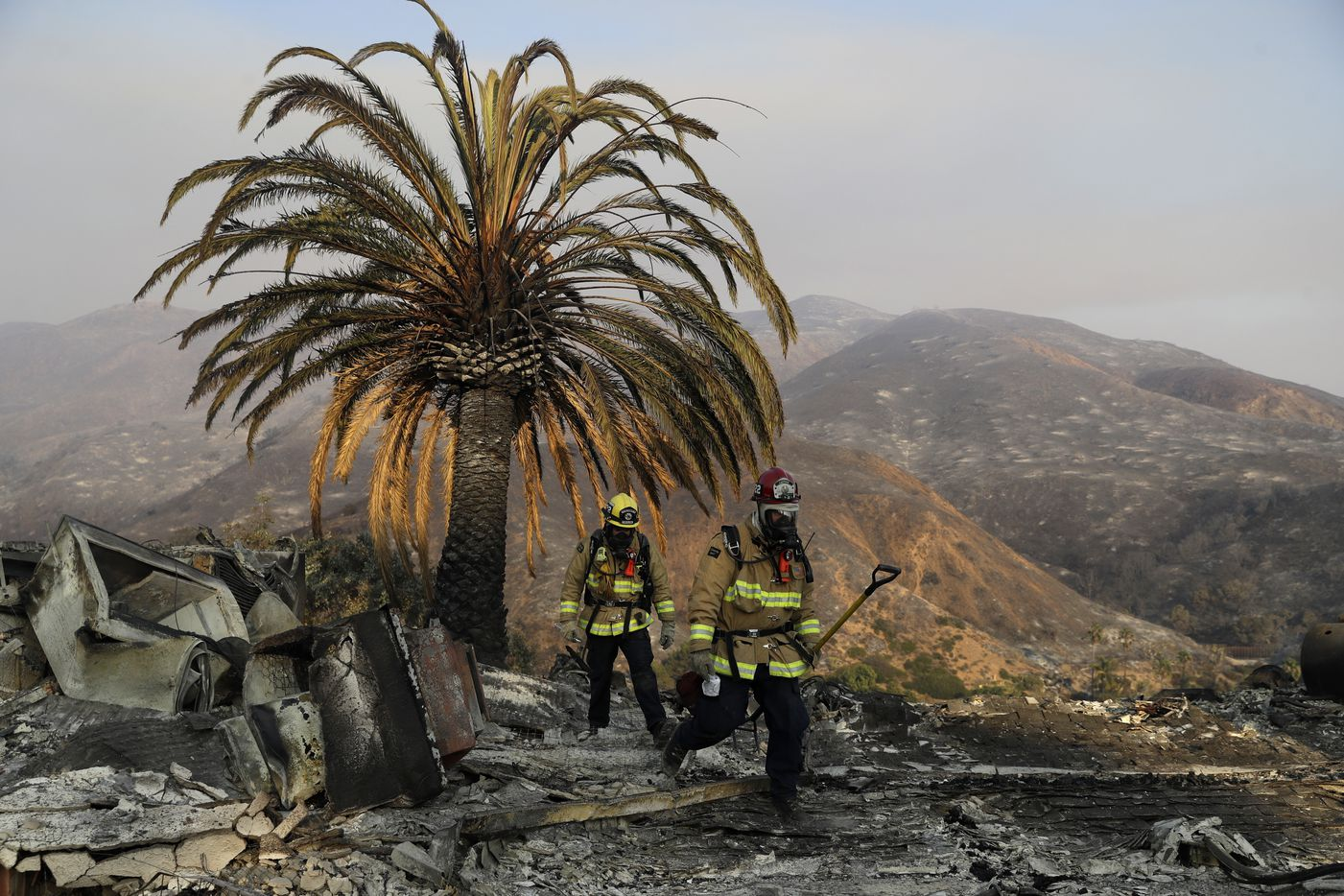 Firefighters Jason Toole (right) and Brent McGill with the Santa Barbara Fire Dept. walk among the ashes of a wildfire-ravaged home after turning off an open gas line on the property on Nov. 10, 2018, in Malibu, Calif.