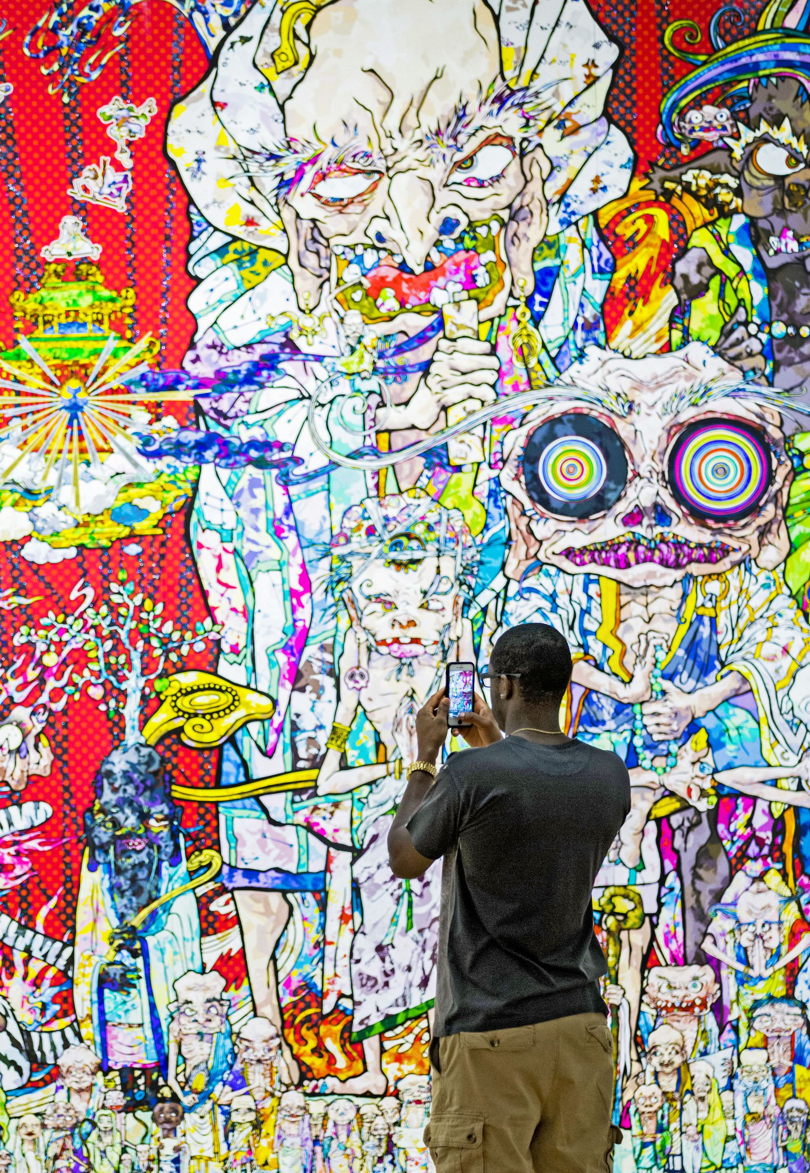 """Dominique Carter takes photos with his cellphone for social media at Takashi Murakami's exhibition, """"The Octopus Eats Its Own Leg,"""" at the Modern Art Museum of Fort Worth on July 20, 2018."""