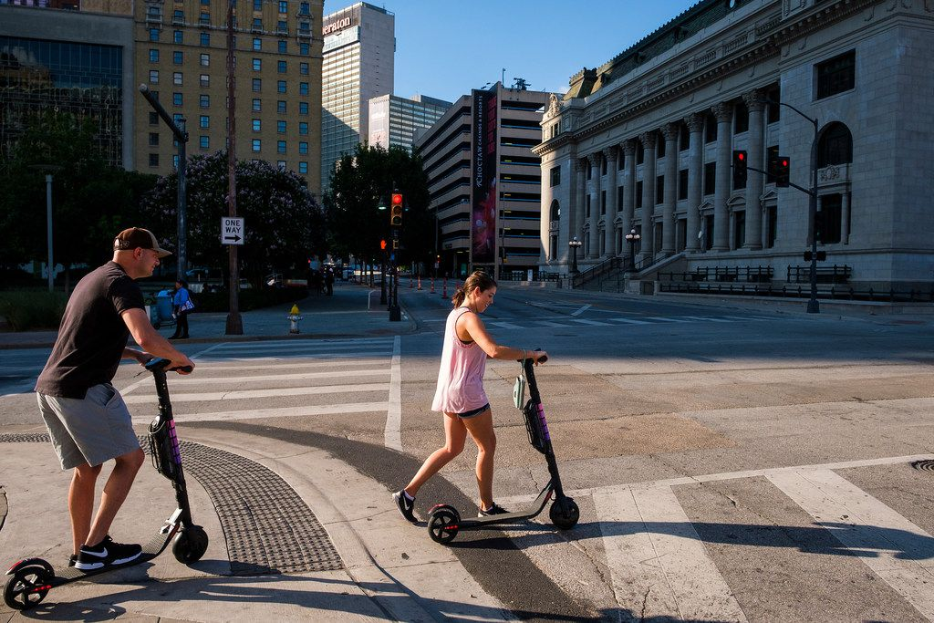 People ride rental scooters along Commerce Street in downtown Dallas. The scooters aren't allowed on sidewalks downtown, and police said they've started enforcing that rule, among others.