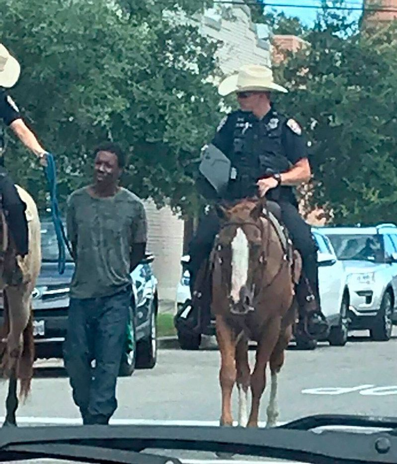 Donald Neely is walked with handcuffs and a rope by two mounted police officers in Galveston on Aug. 3.