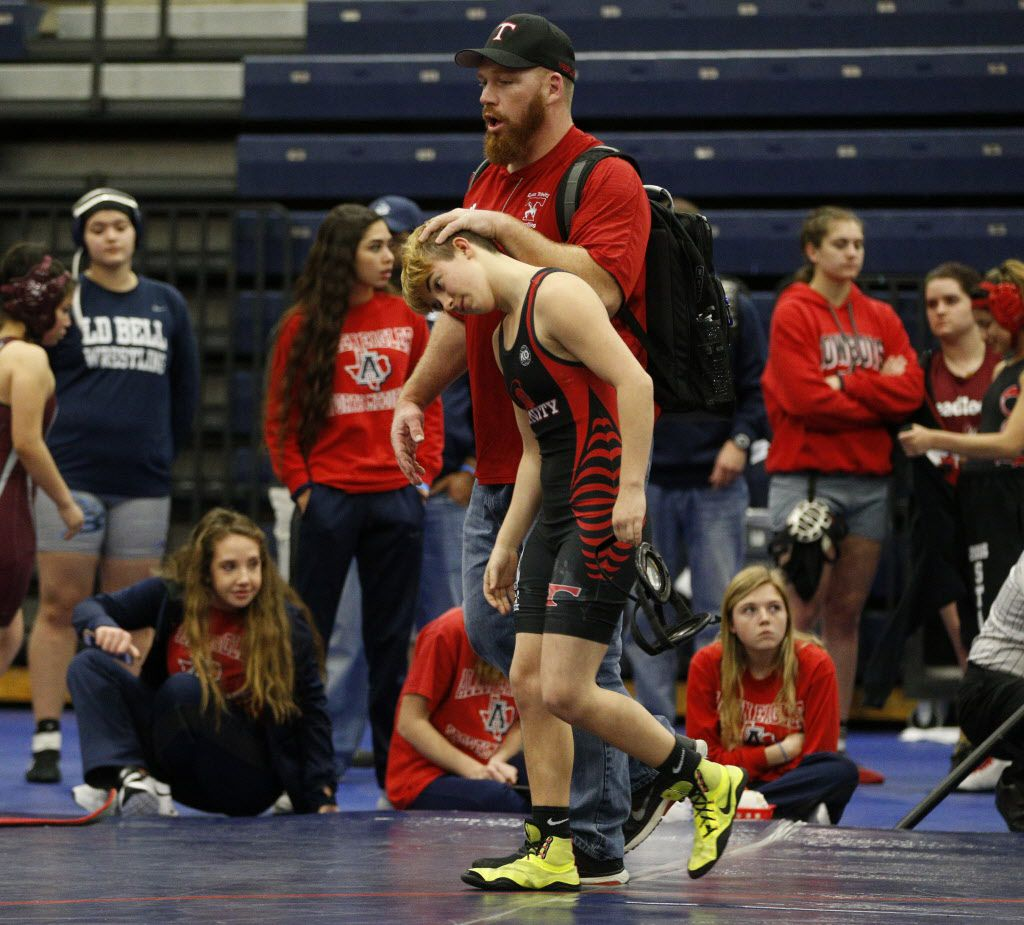Euless Trinity's Mack Beggs (front) walks off the mat with coach Travis Clark after Beggs' opponent forfeited the girls 110-pound Class 6A Region II championship Saturday at Allen High School.