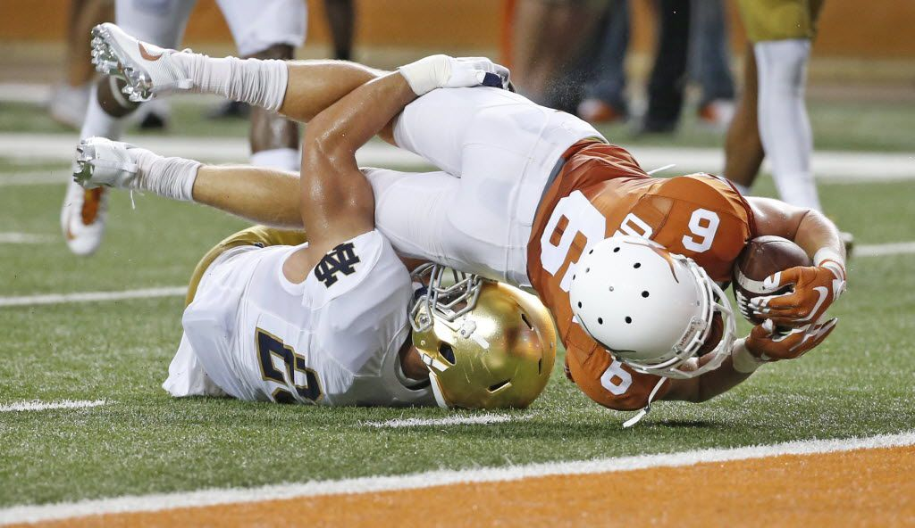 Texas receiver Jake Oliver (6) stretches for the goal line after a second-quarter pass reception as Notre Dame safety Drue Tranquill (23) makes the tackle during the Notre Dame Fighting Irish vs. the University of Texas Longhorns NCAA football game at Darrell K. Royal Memorial Stadium in Austin on Sunday, September 4, 2016. (Louis DeLuca/The Dallas Morning News)