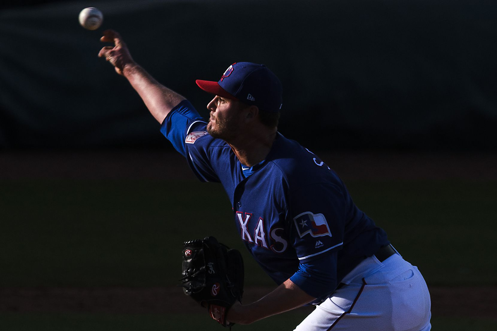 Texas Rangers pitcher Connor Sadzeck throws a pitch as the last rays of sunlight hit the mound during the eighth inning of a spring training game against the Milwaukee Brewers on Feb. 24 at Surprise Stadium in Surprise, Ariz.