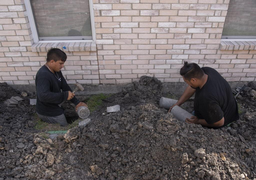 Nelson (izq.) y Asnider Rodríguez, de HD Foundations, trabajan en nivela una casa afectada en sus cimientos. REX CURRY/DMN
