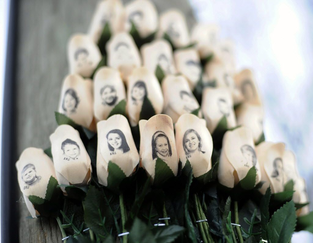 White roses with the faces of victims of the Sandy Hook Elementary School shooting are attached to a telephone pole near the school in Newtown, Conn. (AP Photo/Jessica Hill