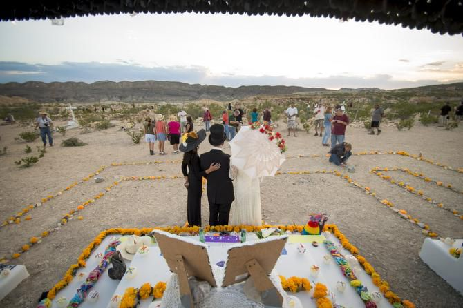 Participants in the Terlingua Ghost Town Dia De Los Muertos celebration pose for a photo in front of one of the alatars in the town's cemetery where residents and visitors gather every year on Nov. 2 for the ritual.