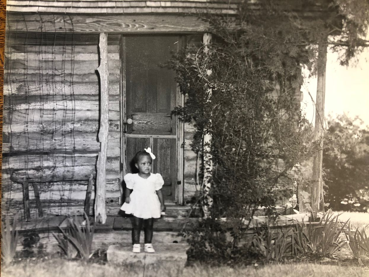 A little girl stands outside a log cabin on Miller farmland in southeast Oak Cliff in this undated photo. The family of plantation owner William Brown Miller used to live in the log cabin before his mansion was completed in 1855. The cabin is now in the Dallas Heritage Village in the Cedars.