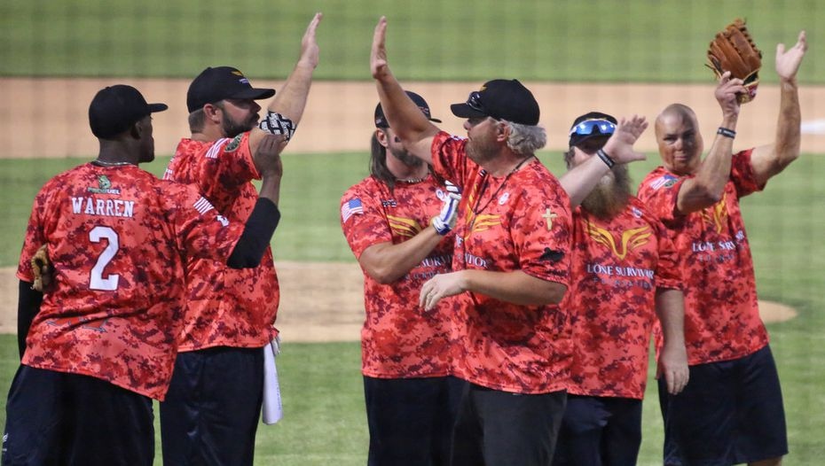 Musician Toby Keith joins teammates during player introductions before the Red River celebrity softball game at the Dr. Pepper Ballpark in Frisco, Texas. (Louis DeLuca/The Dallas Morning News)