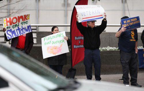 Empleados federales en Dallas muestran pancartas pidiendo apoyo para el fin del cierre del gobierno. ROSE BACA/DMN