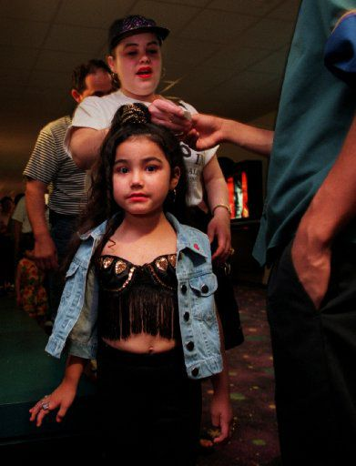 Selena fan Daniella Alvarado, 5, is all  dressed up like her idol for the 7 p.m. showing March 21, 1997, at the AMC Grand at the corner of Northwest  Highway and Stemmons Expressway. Her mom, Clara Alvarado, is  behind her, giving tickets to an usher.
