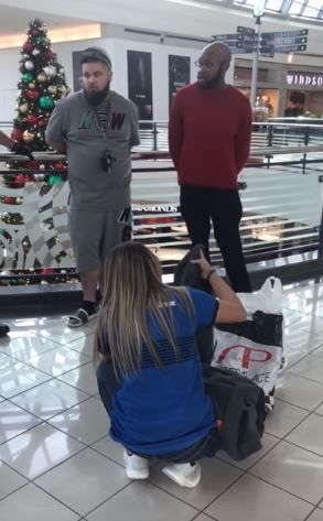 A Finish Line employee goes through bags of items purchased by Ro Lockett (right) and Brandon Kibart (left) at Stonebriar Centre in Frisco.