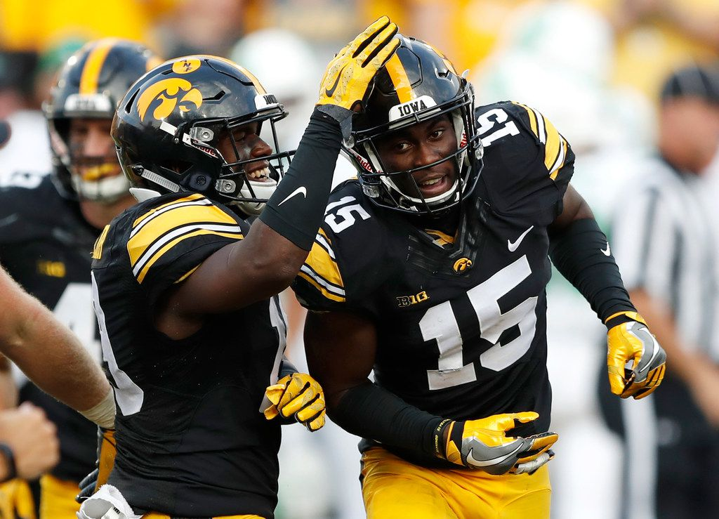FILE - In this Sept. 16, 2017, file photo, Iowa's Josh Jackson (15) celebrates with teammate Miles Taylor, left, after intercepting a pass during the second half of an NCAA college football game against North Texas, in Iowa City, Iowa.  (AP Photo/Charlie Neibergall, File)