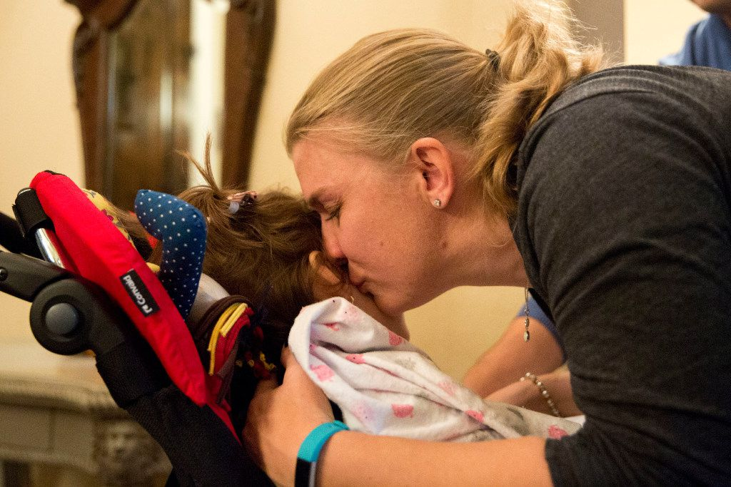 Penny Howard gives Anny Fischer, 8, a kiss after the Fischers of Brazil arrive at the Howard family home in The Colony. (Ting Shen/Staff Photographer)