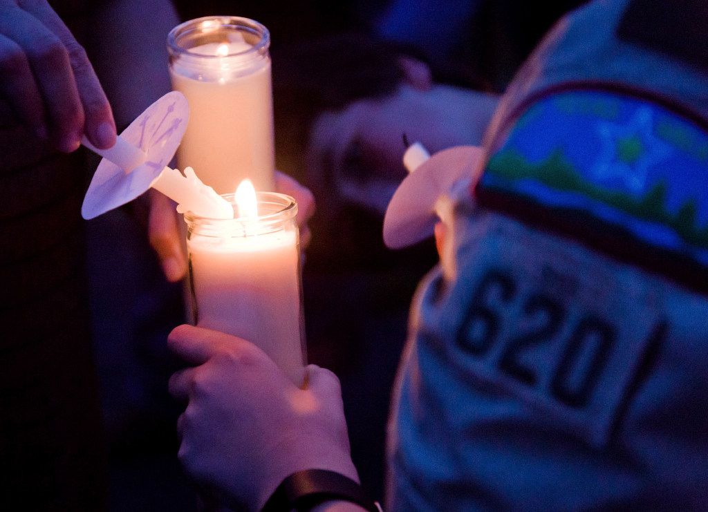 Participants light candles during a candlelight vigil Sunday, August 6, 2017, in Hallsville, Texas, for two Boy Scouts who were killed and another severely injured in a Saturday boating accident.