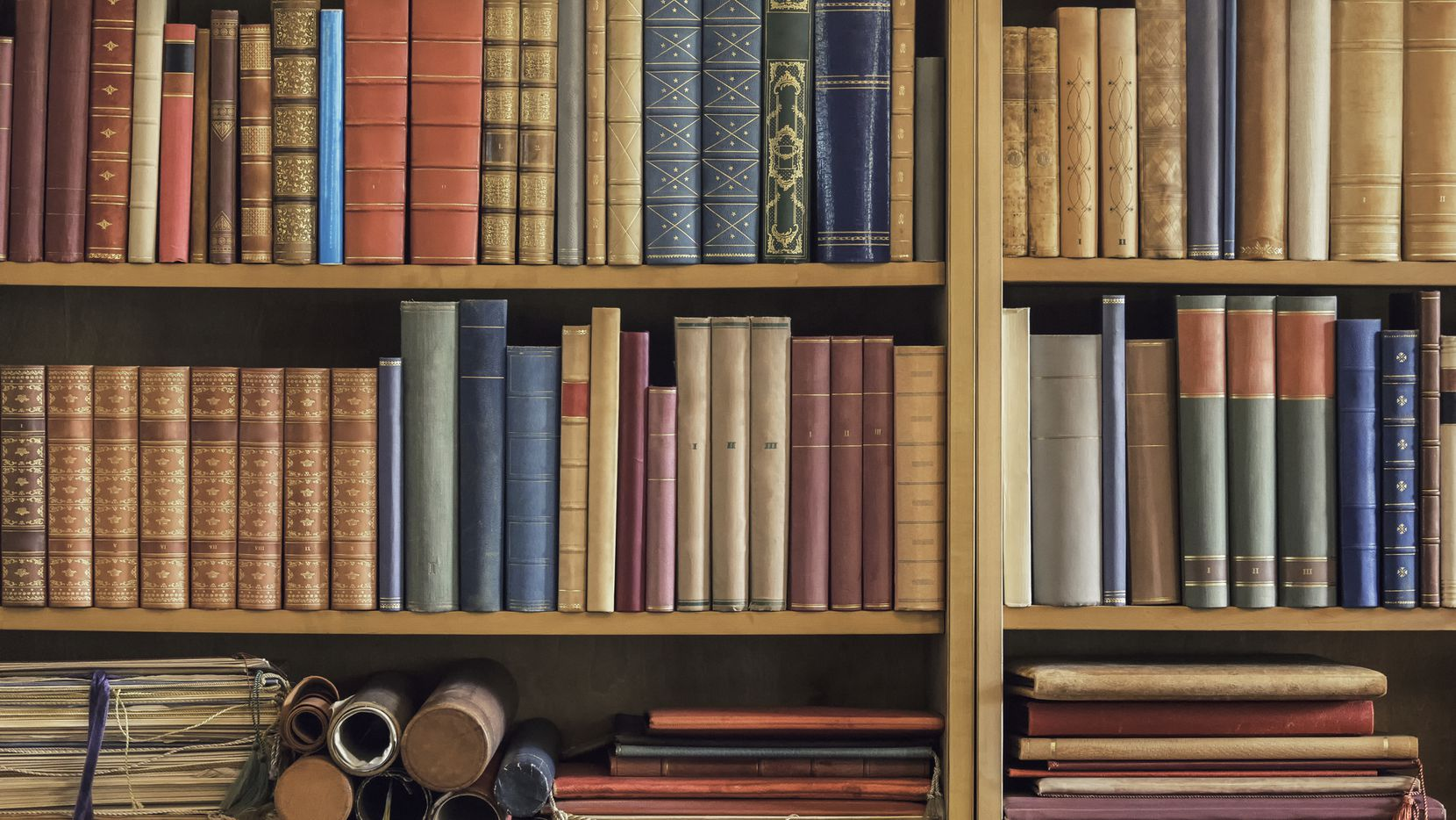 A collection of old books and documents in a shelf.