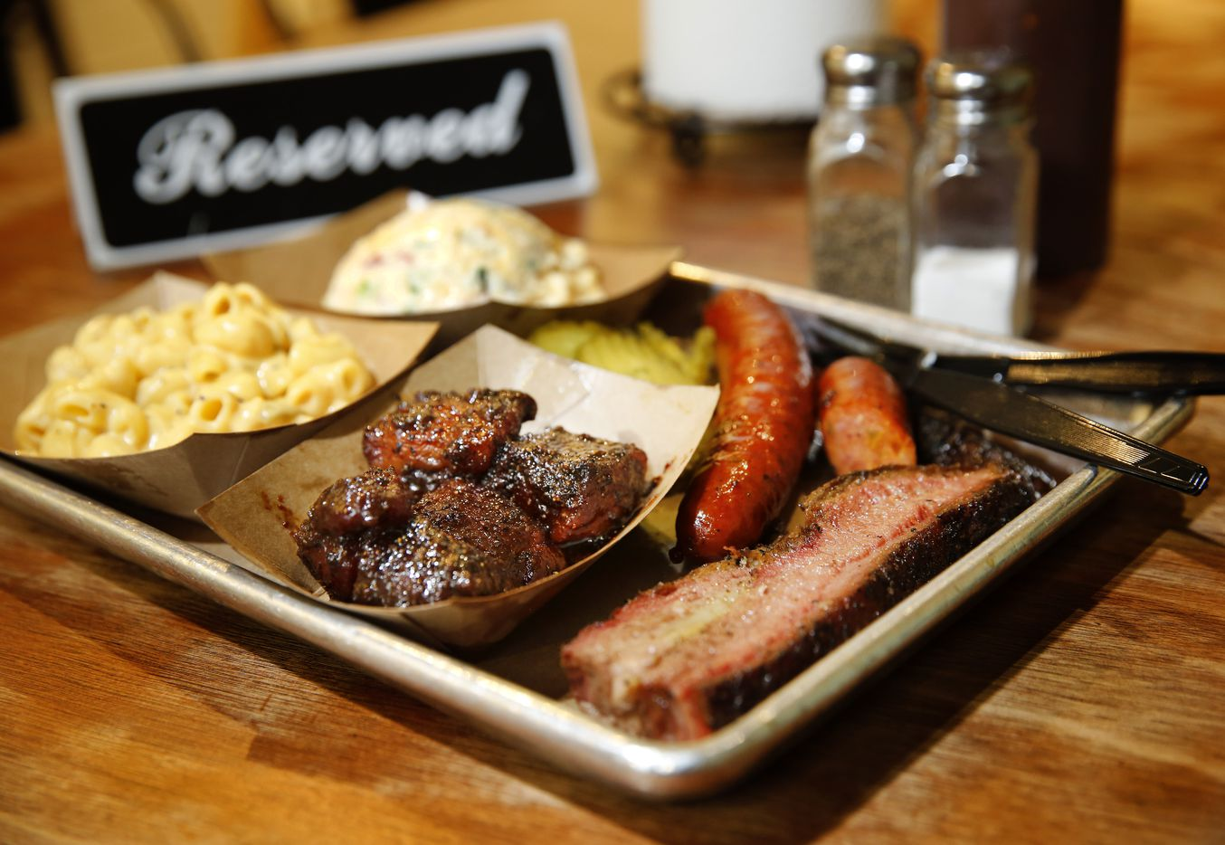 A tray full of C.A.B. brisket, burnt ends, sausage, green chile mac & cheese, and twice baked potato salad are pictured at Heim Barbecue in Fort Worth, Texas.