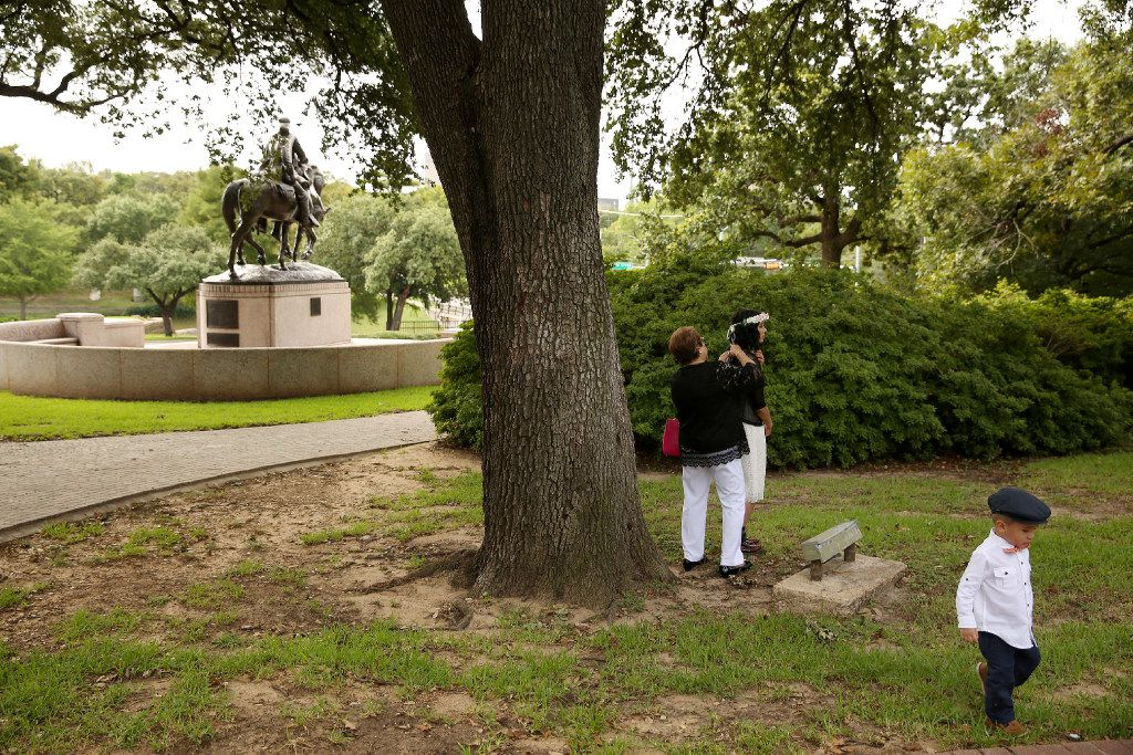 Matthew Chavez, 2, walks by as his mother, Miranda Taddei (in floral headwear), is readied before starting her marriage ceremony to Matthew Chavez near a statue of Confederate Gen. Robert E. Lee at Robert E. Lee Park in the Oak Lawn neighborhood of Dallas on Wednesday, Aug. 16, 2017.