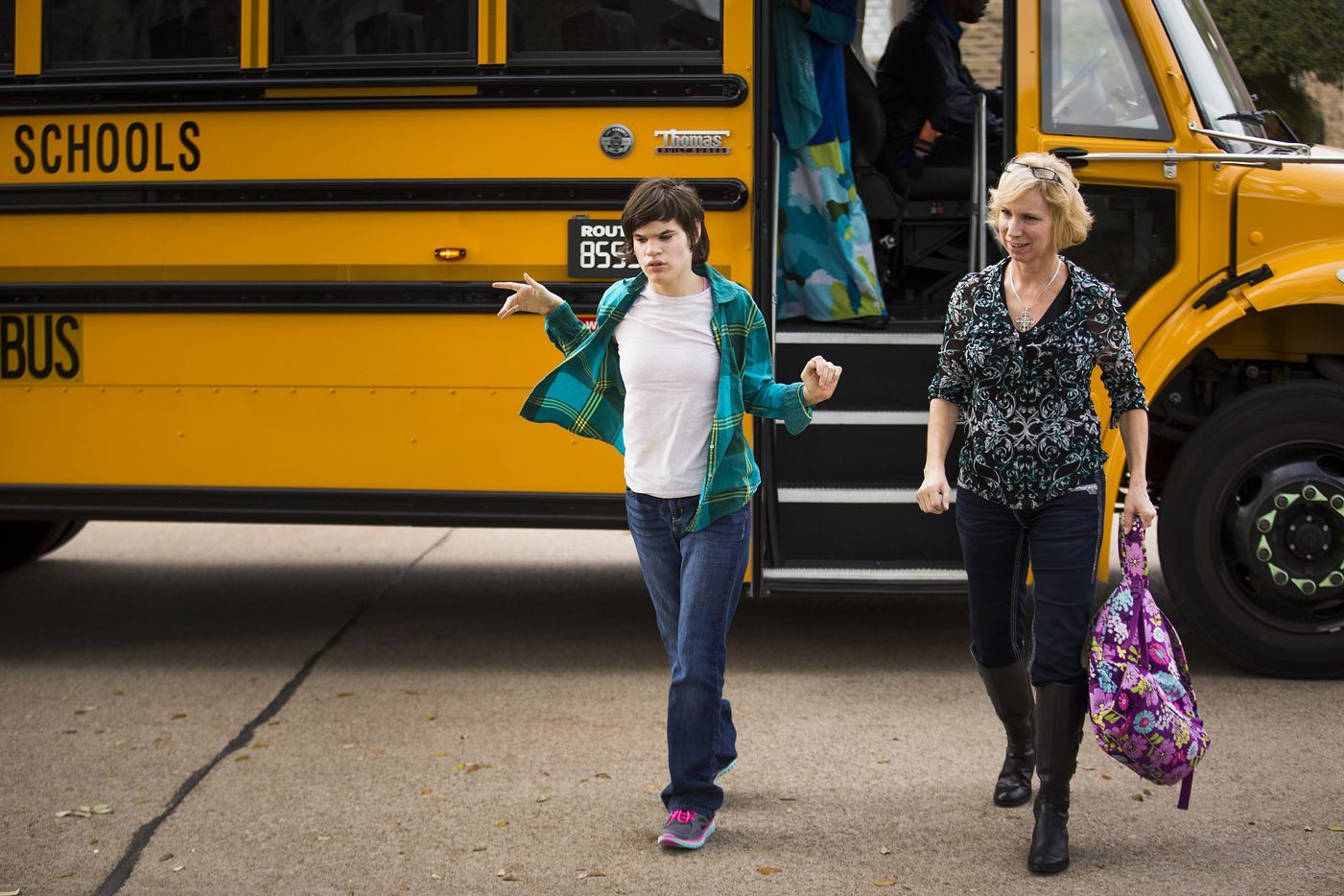 Christy Zartler helps her daughter Kara Zartler off of the school bus in front of her family's home on Thursday, March 9, 2017, in Richardson. The 17-year old has severe autism and cerebral palsy. (Smiley N. Pool/The Dallas Morning News)