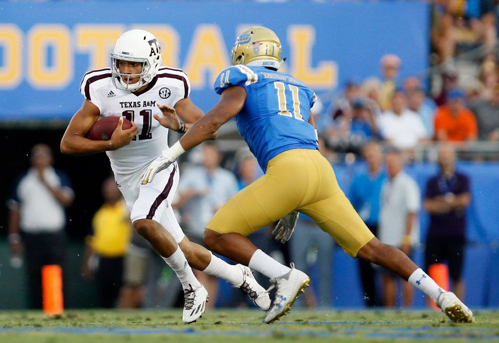 Texas A&M quarterback Kellen Mond, left, scrambles with the ball while UCLA defensive lineman Keisean Lucier-South runs after him during the first half of an NCAA college football game, Sunday, Sept. 3, 2017, in Pasadena, Calif. (AP Photo/Danny Moloshok)