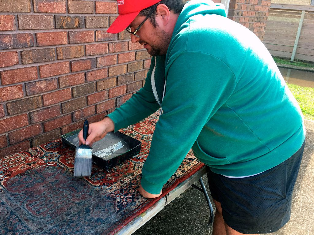 Artist Aaron Angelo paints a rug to make it look as though it has been covered by dirty floodwater for weeks.