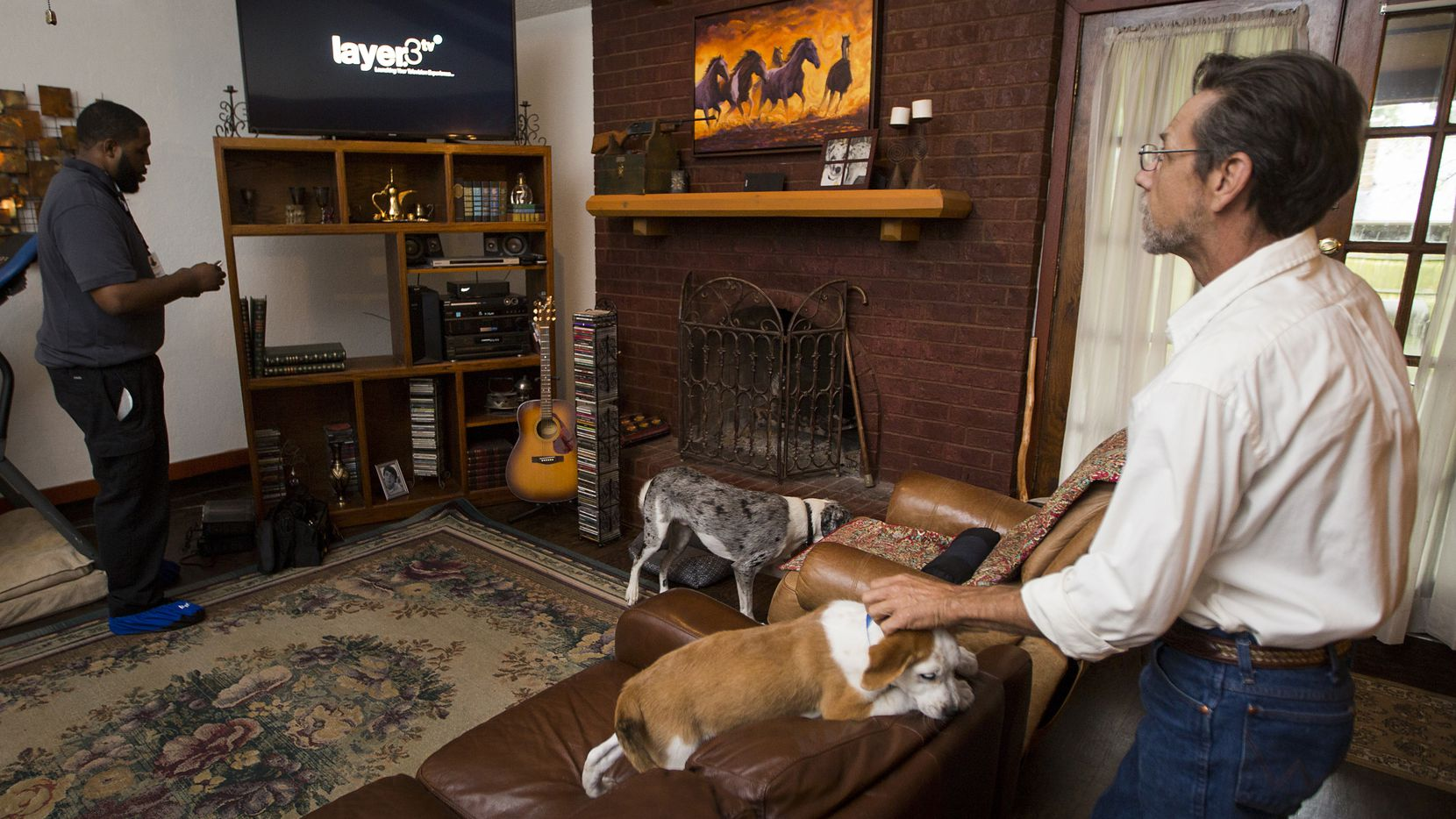 Stevan Grimes scratches his dog Norman as Keith Hamilton of Layer3 installs cable TV equipment at his home on Monday, April 17, 2017, in Benbrook, Texas. Layer3, is a new cable company that has expanded to the Dallas-Fort Worth area.
