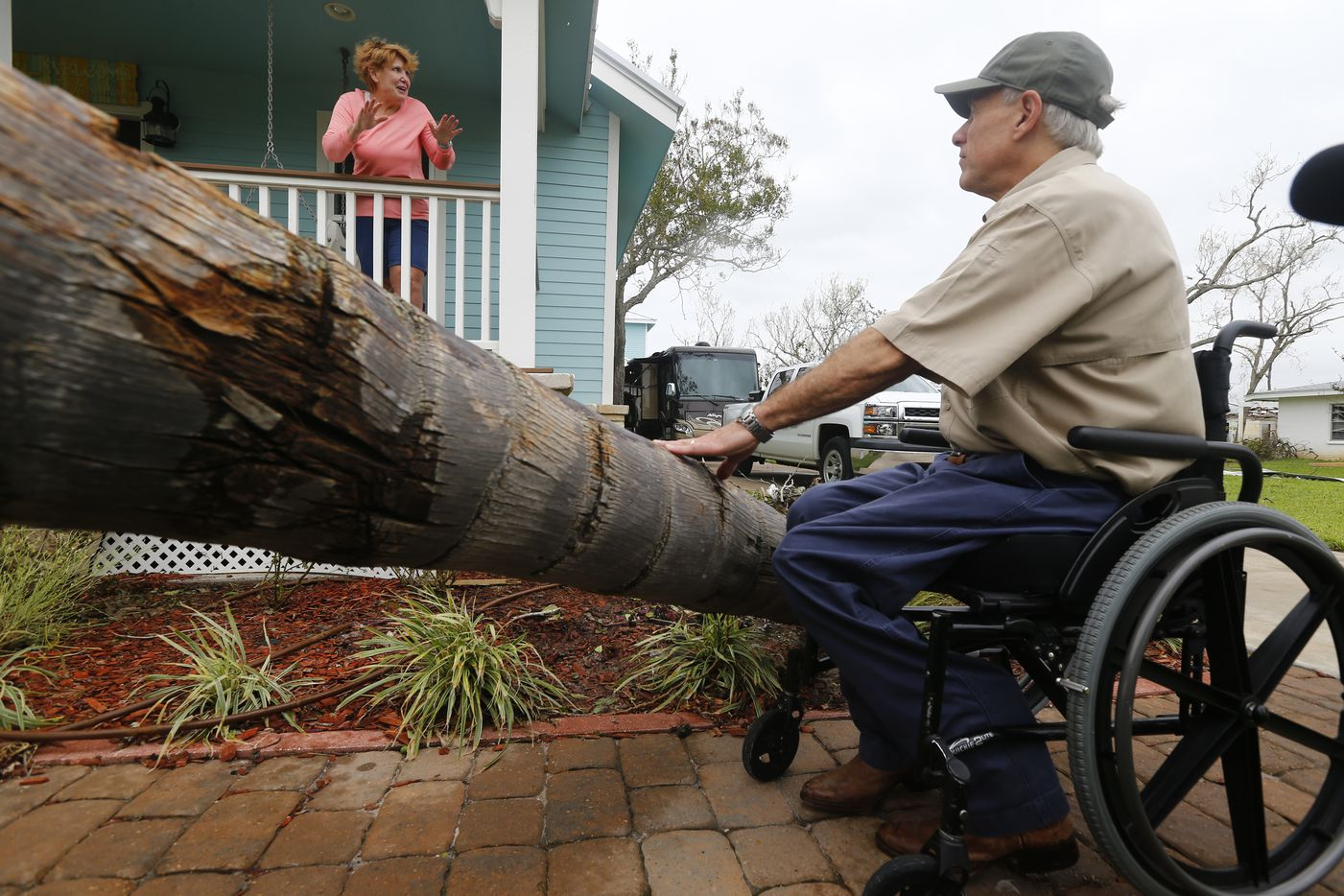 Marsha Brundett tells Texas Gov. Greg Abbott about riding out the storm as he tours damage from Hurricane Harvey in Rockport, Texas on Aug. 28, 2017.
