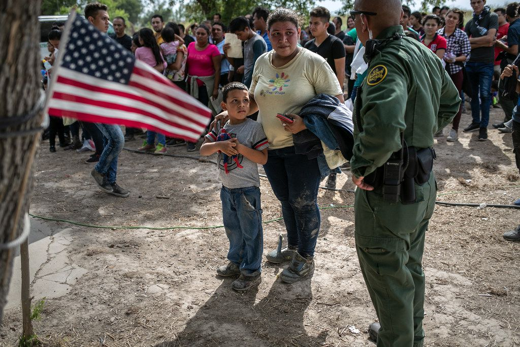 A U.S. Border Patrol agent speaks to immigrants after taking them into custody on July 2, 2019 in Los Ebanos, Texas. Hundreds of immigrants, most from Central America, turned themselves in to border agents after rafting across the Rio Grande from Mexico to seek political asylum in the United States. They were then to be sent to a Border Patrol processing center in McAllen.