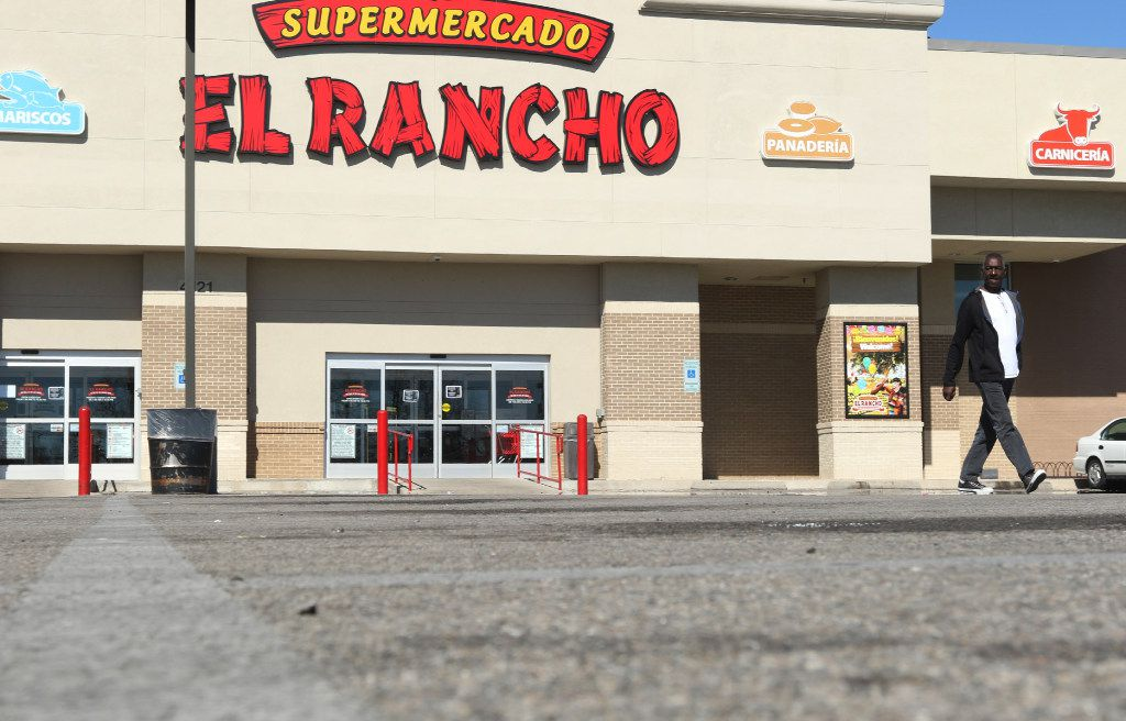 """Glen Knight walks across an empty parking lot after reading a sign, in English and Spanish, on the door of Supermercado El Rancho, on 4121 Gaston Ave, in Dallas, informs their customers that their store would be closed in support of the """"Day Without Immigrants"""" protest. (Irwin Thompson/The Dallas Morning News)"""