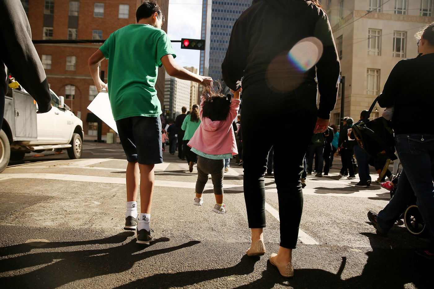 A small child is lifted as marchers move through downtown during the North Texas March for Life in Dallas Saturday.