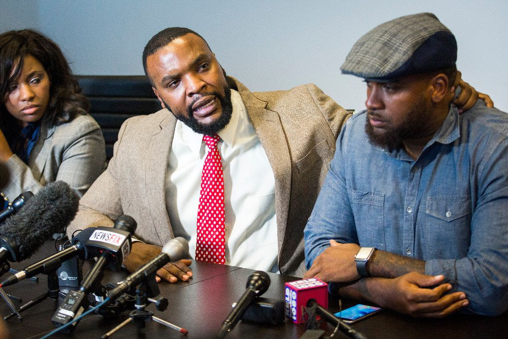 Attorney Lee Merritt (center), who represents Jacqueline Craig, grabs activist Cory Hughes by the neck in a demonstration of force he says was used against his client's son during a press conference Thursday in Dallas.
