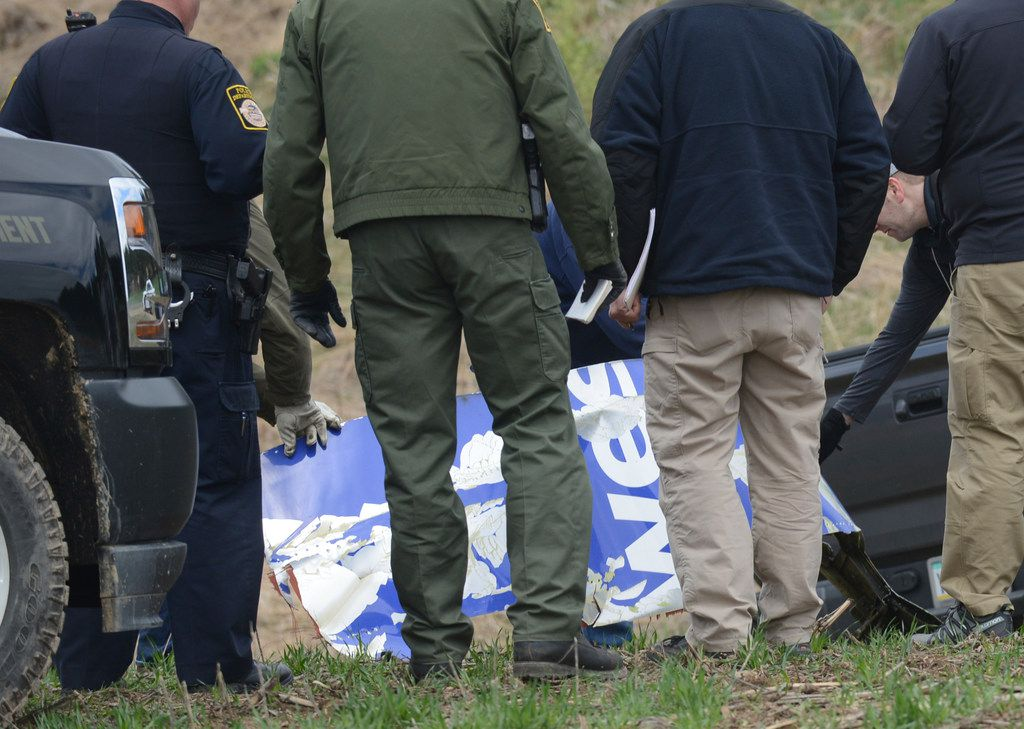 National Transportation Safety Board investigators in Penn Township on Wednesday examine a piece of debris from the Southwest Airlines plane that made an emergency landing Tuesday after a fatal engine mishap.