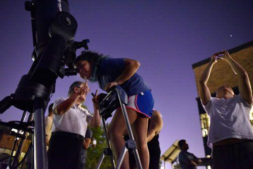 Aubreigh Lares se para en una pequeña escalera para poder ver los planetas a través de un telescopio. (BEN TORRES/ESPECIAL PARA AL DÍA)