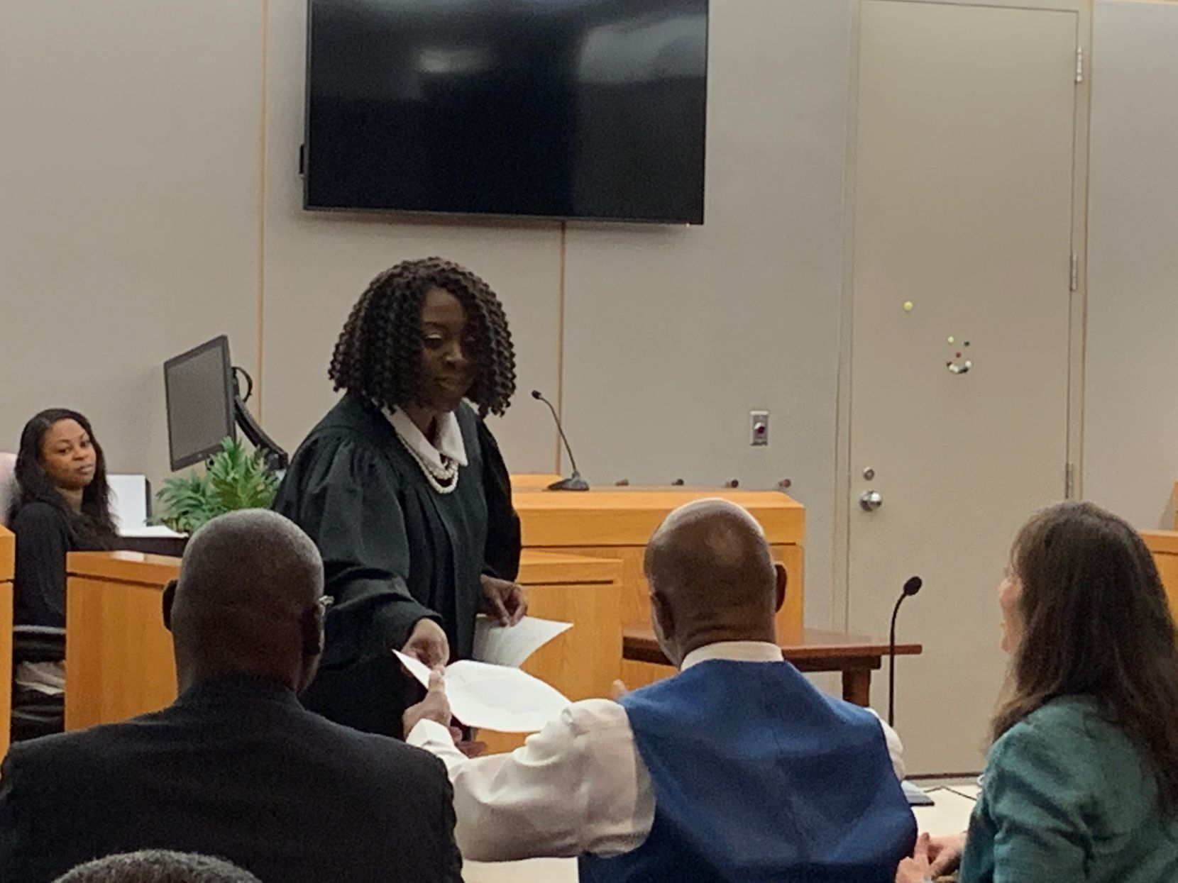 """State District Judge Raquel """"Rocky"""" Jones hands Dennis Allen the paperwork that shows she declared him """"actually innocent"""" of capital murder Friday. Jones also declared Stanley Mozee (left) actually innocent. Sitting next to Allen is attorney Nina Morrison of the Innocent Project in New York."""